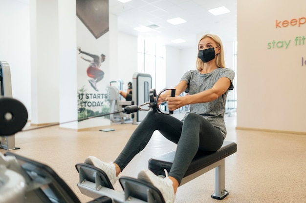 Woman with medical mask working out at the gym during the pandemic