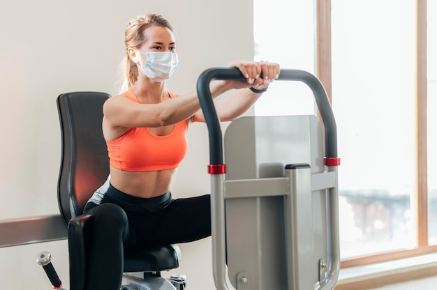 Woman with medical mask working out at the gym