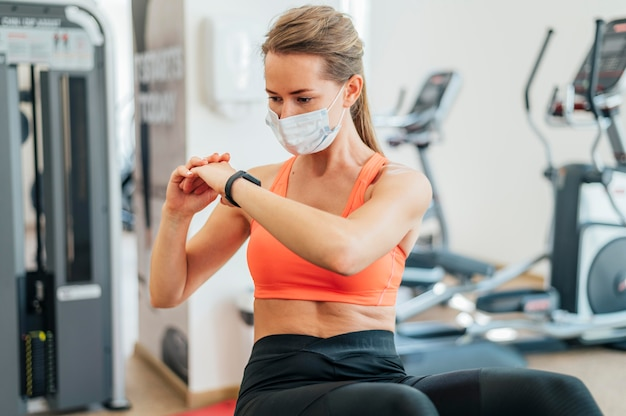 Woman with medical mask working out
