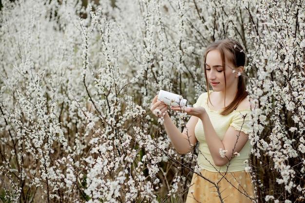 Женщина с лекарством в руках борется с весенней аллергией на открытом воздухе - портрет аллергической женщины в окружении сезонных цветов