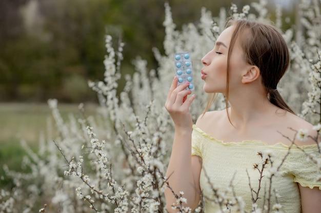 薬を手にした女性 春のアレルギーと闘うアウトドア – 季節の花に囲まれたアレルギーの女性のポートレート。