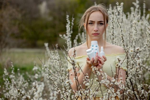 Женщина с лекарством в руках борется с весенней аллергией на открытом воздухе