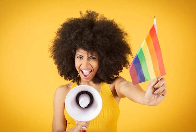 A woman with megaphone afro hair holds the lgbtq gay pride flag she fights for sexual freedom.