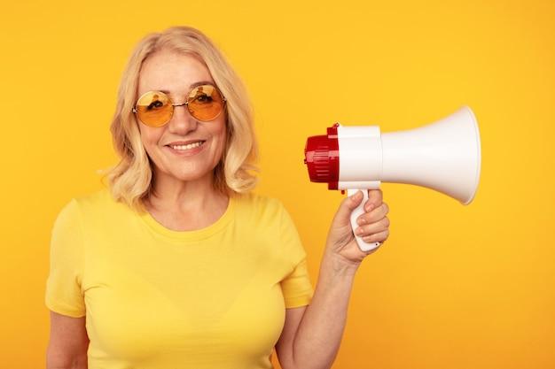 黄色いスタジオで隔離されたメガホンを持つ女性。