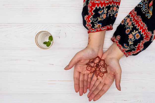 Woman with mehendi on palms near cup with plant twig