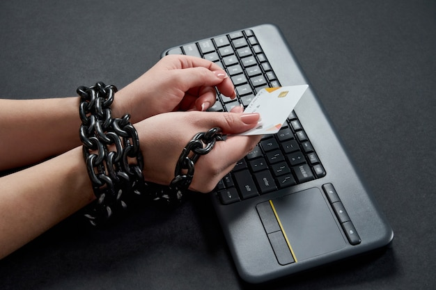 Woman with metal chain holding credit card over keyboard, online shopping addiction concept