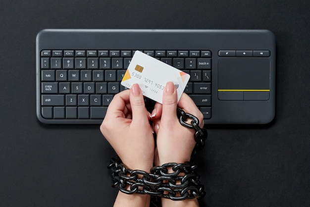 Woman with metal chain holding credit card over keyboard