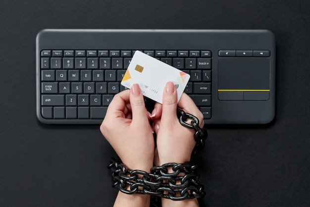 Женщина с металлической цепью держит кредитную карту над клавиатурой, онлайн покупок наркомании концепции