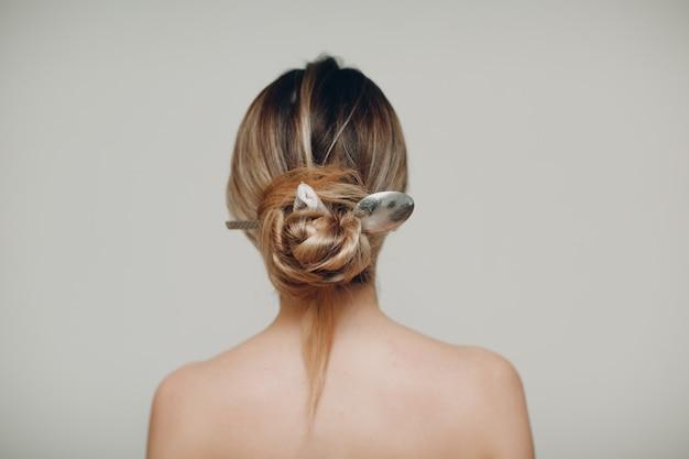 다시 그녀의 헤어 스타일 머리에 금속 숟가락을 가진 여자