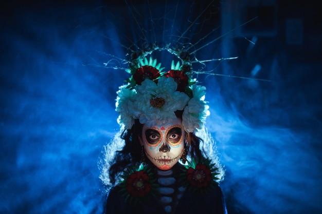 그녀의 얼굴에 멕시코 해골 할로윈 화장을 한 여자. 죽은 자의 날과 할로윈