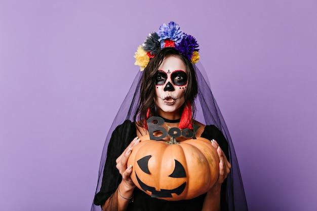 Una donna con una faccia in stile messicano sta cercando di spaventare. bruna con zucca e velo da sposa nero in posa sulla parete lilla.