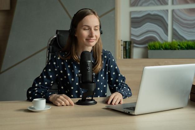 Женщина с микрофоном и портативным компьютером разговаривает и записывает подкаст в студии