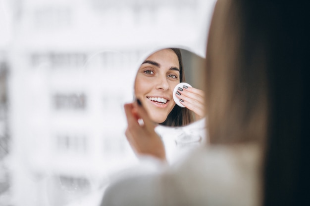 Woman with mirror removing makeup with pad