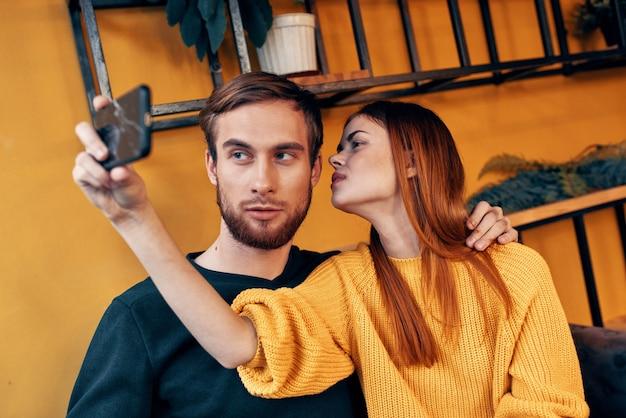 携帯電話を持つ女性と幸せな男の友達楽しい家族のコミュニケーションインテリア