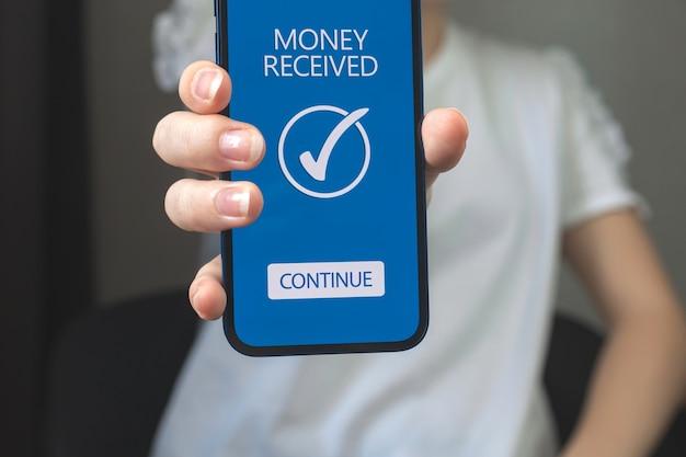 휴대폰과 돈을 받은 여성, 전자상거래와 온라인 뱅킹의 개념, 지불 이체 사진