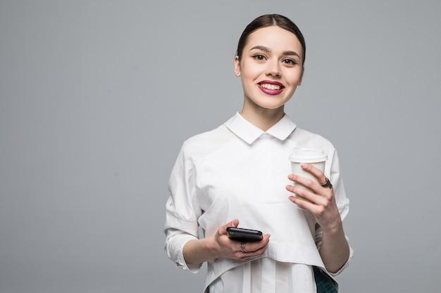 Donna con cellulare e caffè su bianco