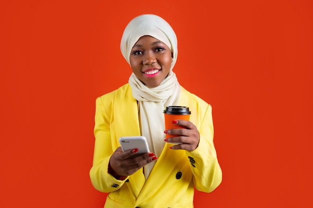 Woman with a mobile phone and a cup of coffee
