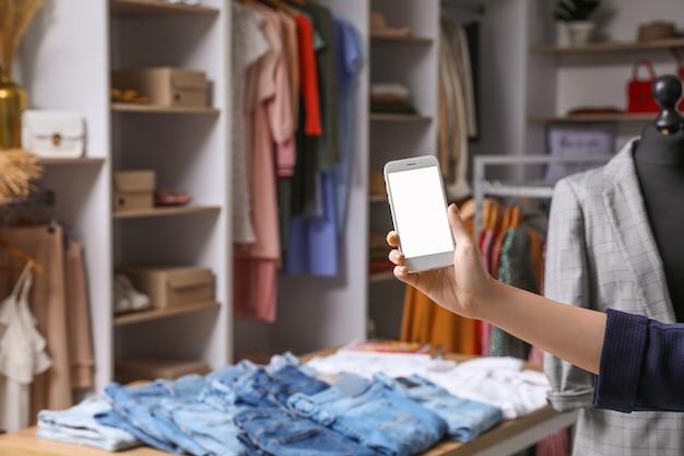 현대 옷이 게에서 휴대 전화를 가진 여자