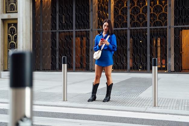 横断歩道の街で携帯電話を持つ女性