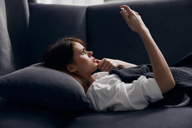 Женщина с мобильным телефоном лежит на диване в помещении комфорт интерьера