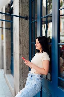 Женщина с мобильным телефоном смотрит в сторону, опираясь на стену