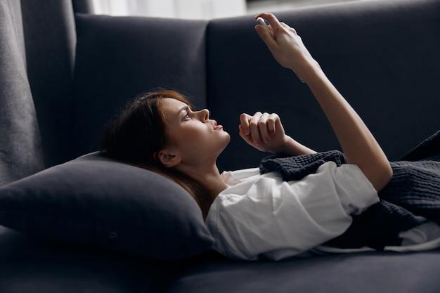 Женщина с мобильным телефоном, лежа на диване в помещении.