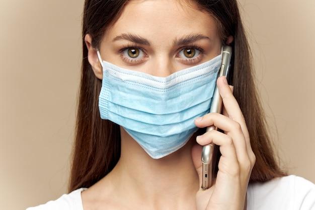 耳医療マスク健康安全と保護の近くに携帯電話を持つ女性