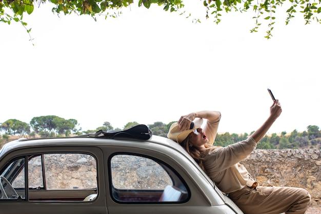 レトロな車の近くの携帯電話を持つ女性