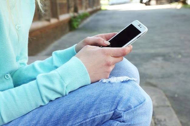 携帯電話を持つ女性、屋外 Premium写真