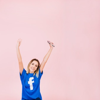 Woman with mobile phone raising her arms on pink background