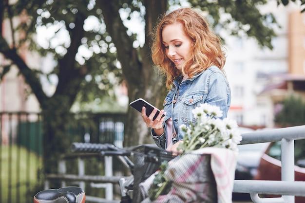 Женщина с мобильным телефоном, расслабляющаяся после езды на велосипеде