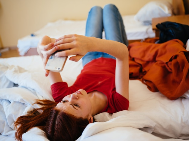 Женщина с мобильным телефоном пишет сообщение модель красной футболке кровать