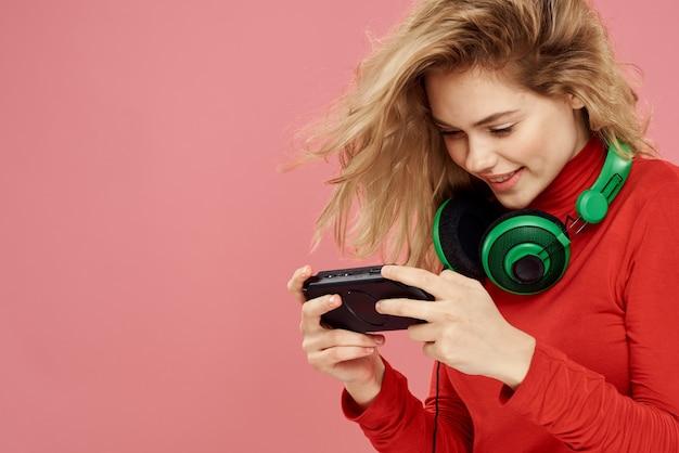 Женщина с мобильными наушниками телеприставки, играя в розовую стену красной куртке образа жизни.