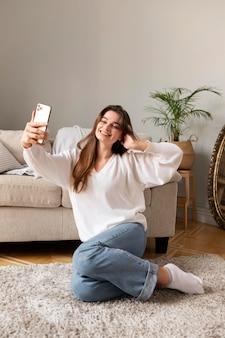 Donna con cellulare prendendo selfie