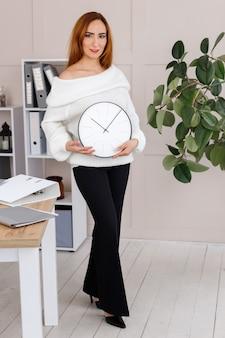 オフィスで手にモック時計を持つ女性