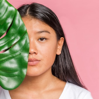 Woman with monstera leaf looking at camera