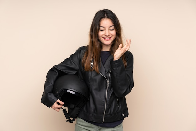 Woman with a motorcycle helmet on beige wall unhappy and frustrated with something