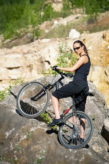 A woman with a mountain bike enjoys the view