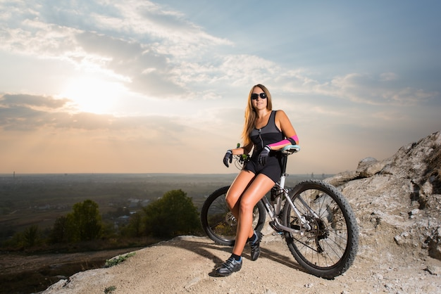 Woman with the mountain bike on the rock cliff under a sky at sunset