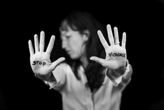 Woman with mouth closed with patch and hands that says stop violence