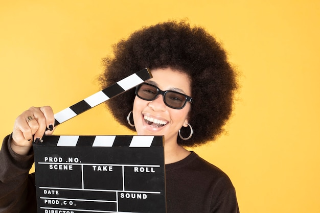 Woman with movie clapperboard yellow background