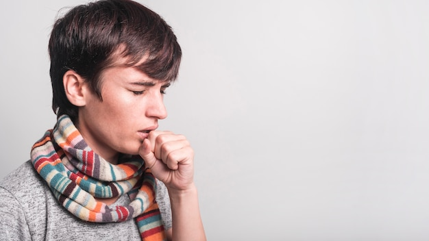 Woman with multicolored scarf around her neck coughing against gray backdrop