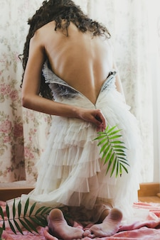 Woman with naked back holding leaf