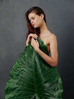 裸の体を持つ女性は大きな緑の葉で覆われています