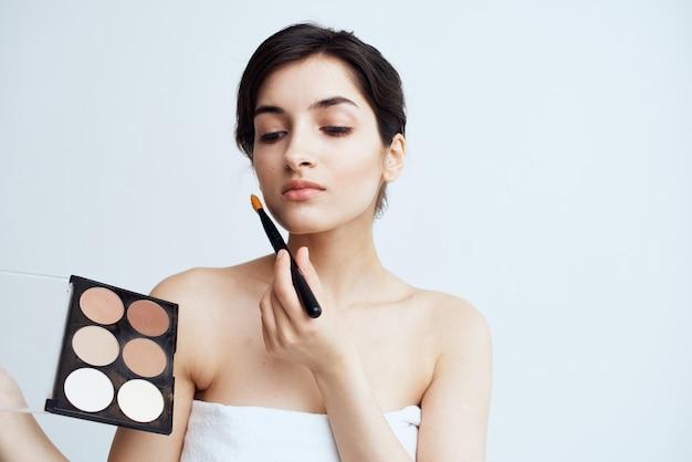 顔に化粧をしている裸の肩の化粧品を持つ女性