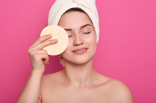 Woman with naked shoulders, holding sponge for applying makeup foundation, female standing in bathroomwith