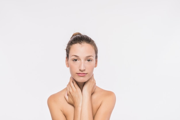 Woman with naked shoulders touching neck