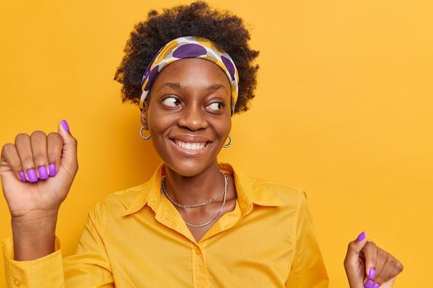La donna con i capelli ricci naturali ha danze d'umore ottimistiche e tiene le braccia alzate indossa la camicia con la fascia in posa su un giallo vivido
