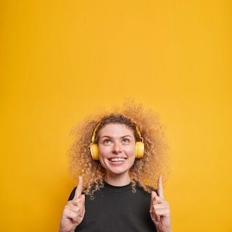 自然な巻き毛の笑顔を持つ女性は、人差し指で上の白い歯のポイントを積極的に示しています陽気な表情を持っていますワイヤレスヘッドフォンポーズを介して音楽を聴きます