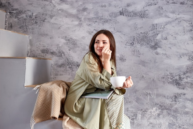 彼女の家の階段に座っている間朝の日光を楽しんでいる自然なそばかすを持つ女性。